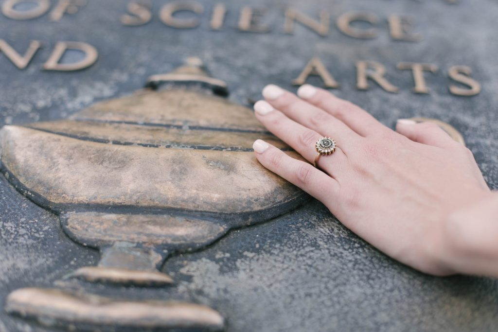 A hand wearing the Women's Dinner Ring places its hand over the Auburn Seal.