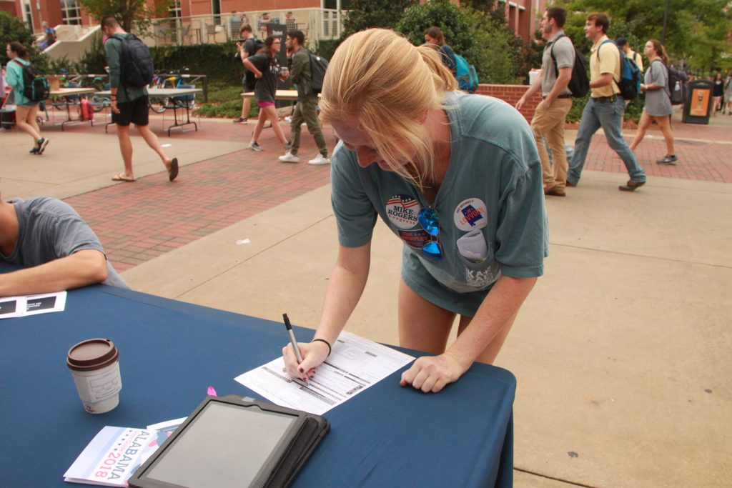 Student at voter registration event fills out a voter registration form.