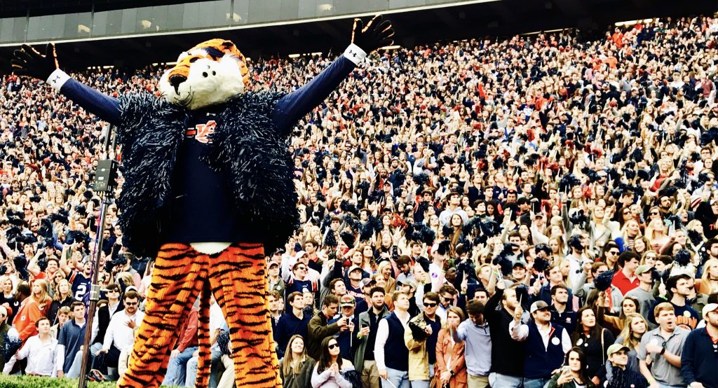 Aubie at Gameday looks out onto the field, with his arms out stretched. Aubie is wearing his navy blue shaker vest and is standing in front of a packed student section.