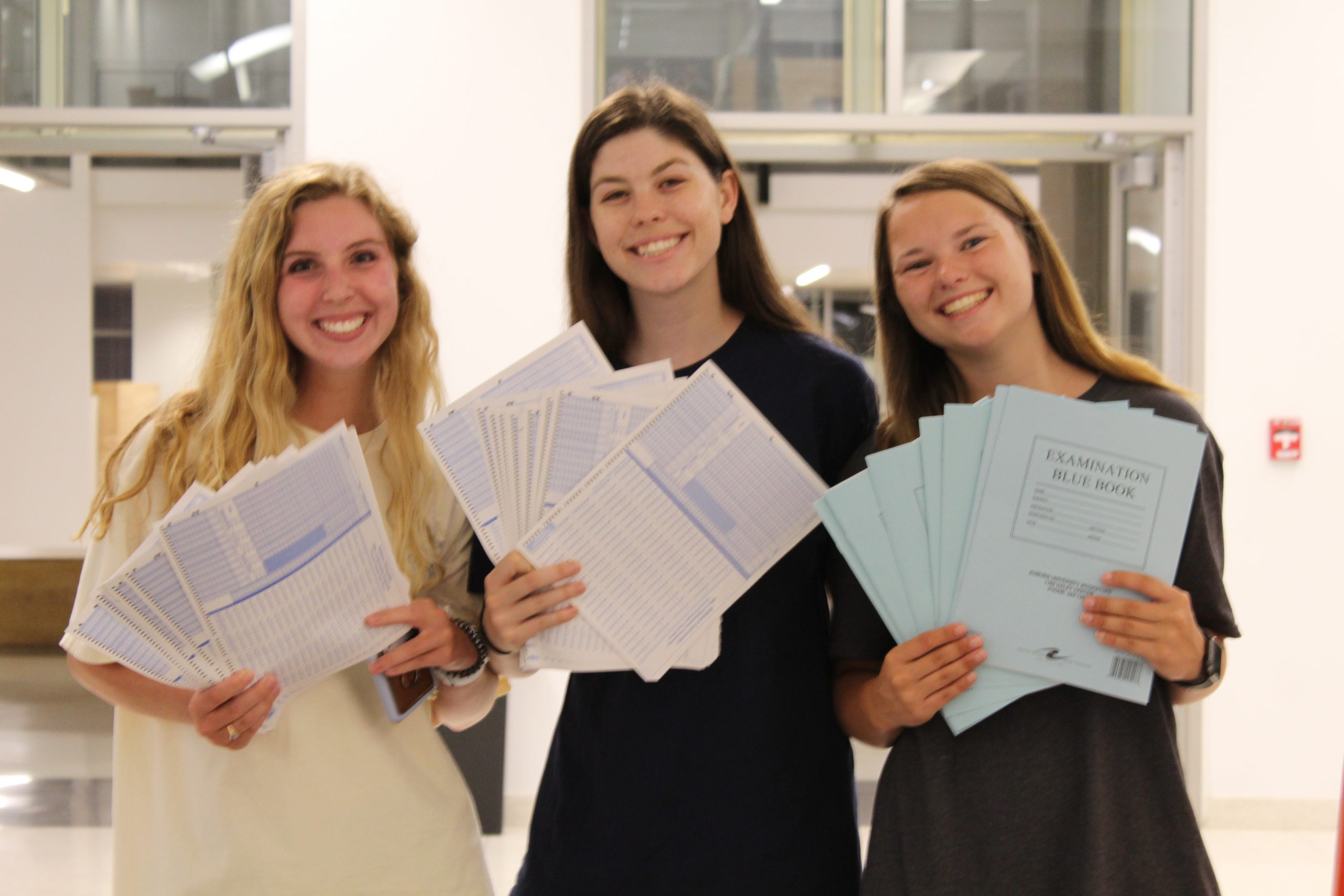 Three Student Government Association members stand in the Mell Classroom Building at a past Up All Night. They are holding scantrons and Blue Books that they passed out to students as they prepare for finals.