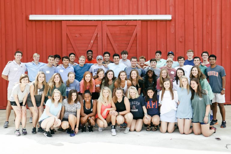 Former freshman forum members are grouped together for a team photo. They are in front of Auburn's Red Barn- where they held the Freshman Forum retreat that year.