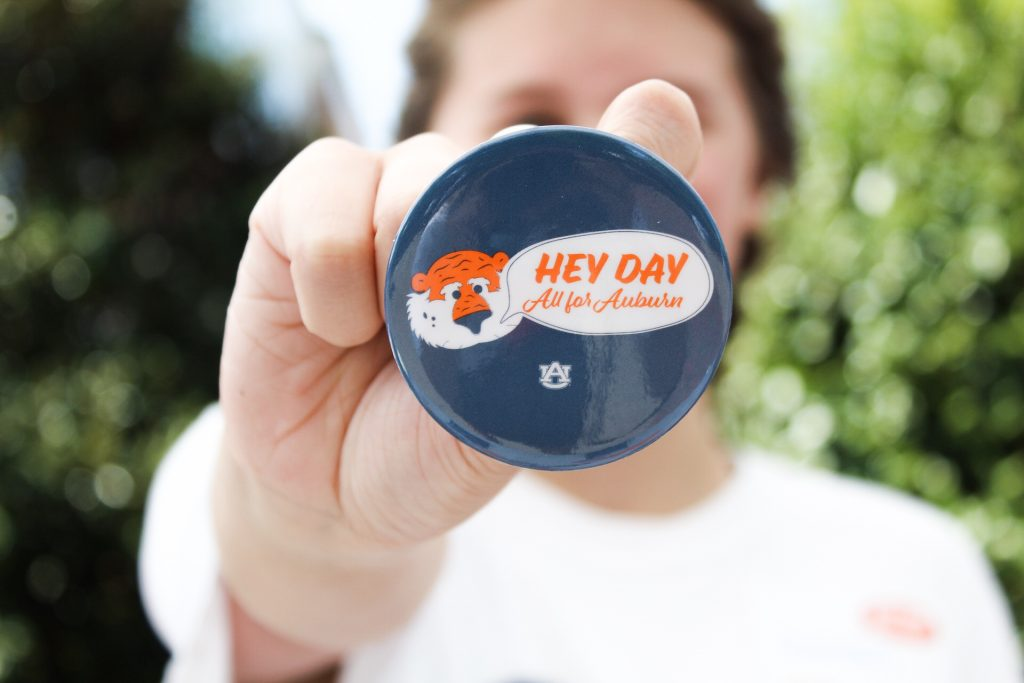 "Hey Day volunteer is holding a Hey Day button. The button is in the foreground and focused in- the button has Aubie with a speech bubble saying the year's theme: ""Hey Day, All for Auburn""."
