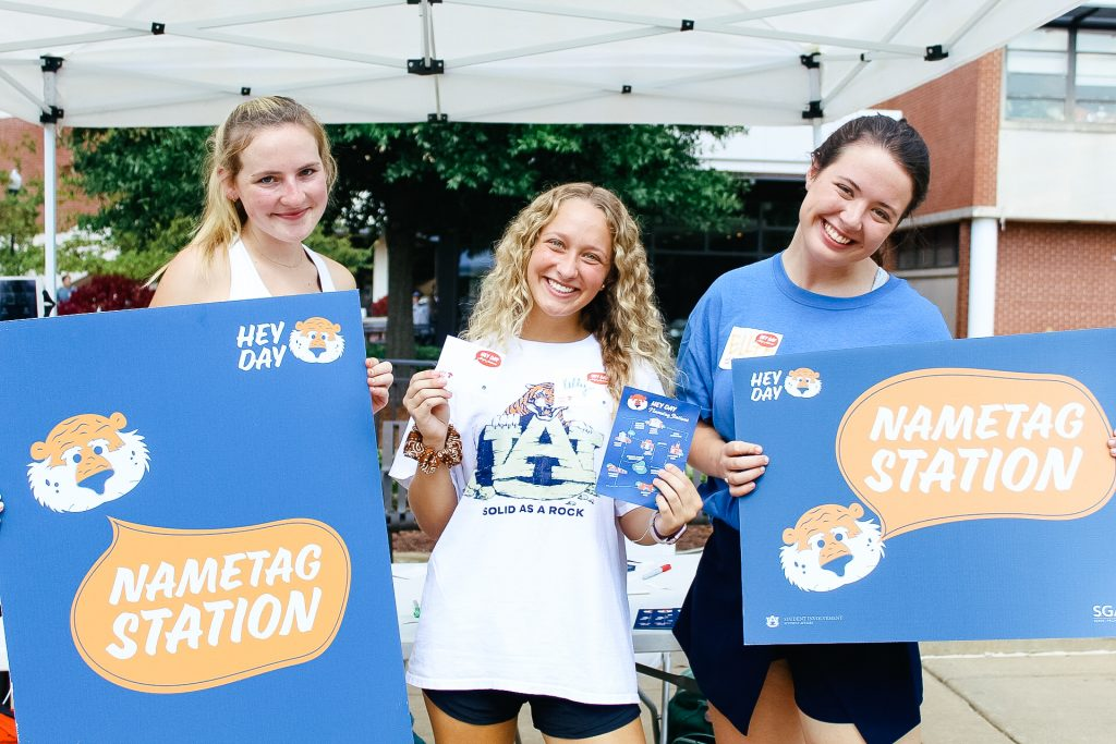 "Three Hey Day volunteers stand near a name tag station. Two are holding name tag station signs. The signs have Aubie on them with a speech bubble saying ""name tag station"" The volunteer in the middle is holding a Hey Day name tag."