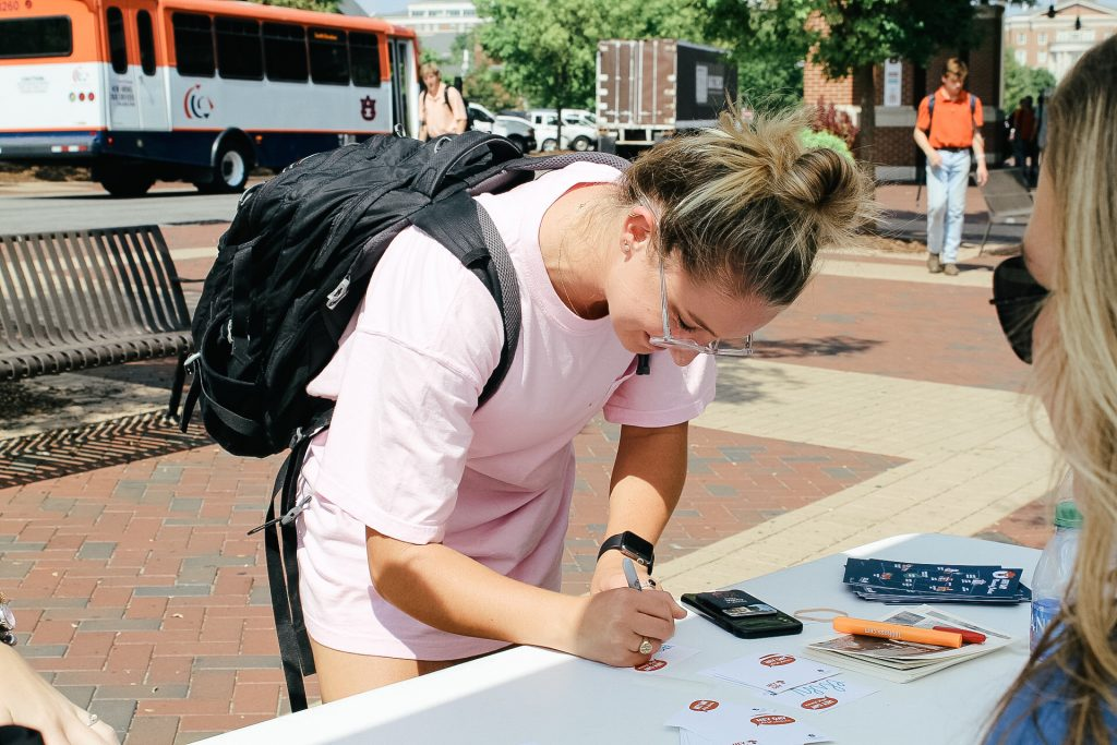 Auburn student is smiling as they fill out a Hey Day name tag at a name tag station.