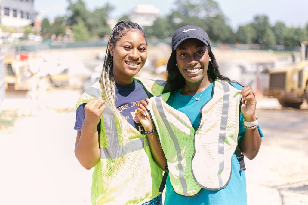 Two Student Government Association members stand in front of a current construction site on campus. They are wearing safety vests to help promote Safety Week.