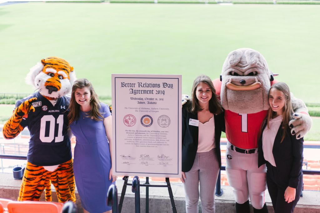 Student Governance Leaders from Auburn University, University of Alabama and University of Georgia stand next to their respective mascots after signing the Better Relations Day agreement. Which is standing between the leaders, on an easel.