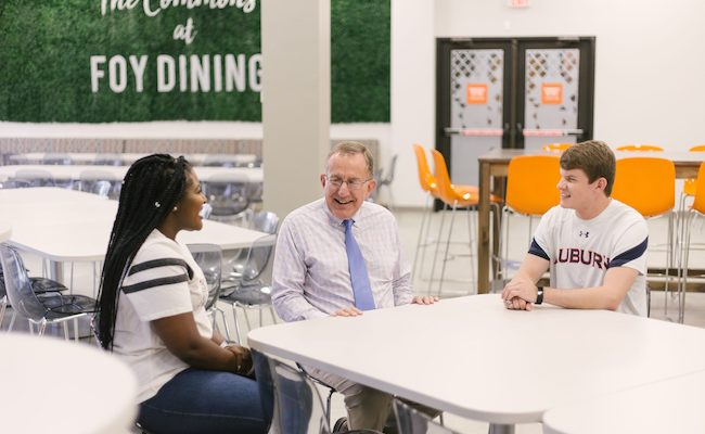 Two Student Government Association members sit with a faculty member as they participate in the Flunch- Faculty Lunch- program.